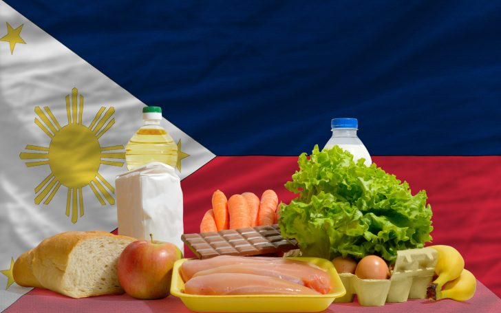 complete national flag of philippines covers whole frame, waved, crunched and very natural looking. In front plan are fundamental food ingredients for consumers, symbolizing consumerism an human needs