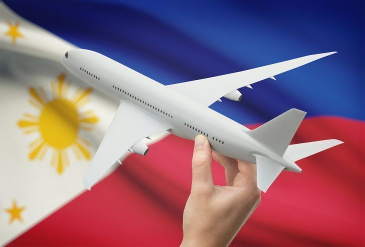 Airplane in hand with national flag on background - Philippines